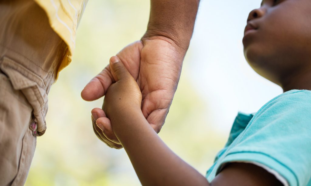 Homem e criança dão as mãos
