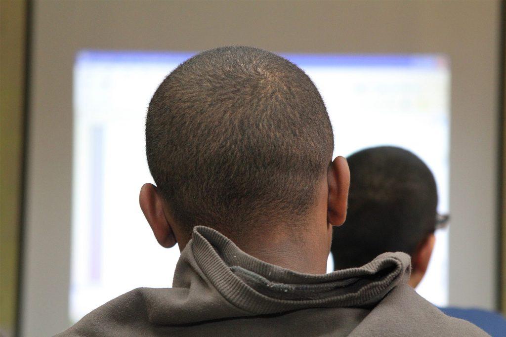 Imagem mostra garoto com a cabeça raspadas e de costas