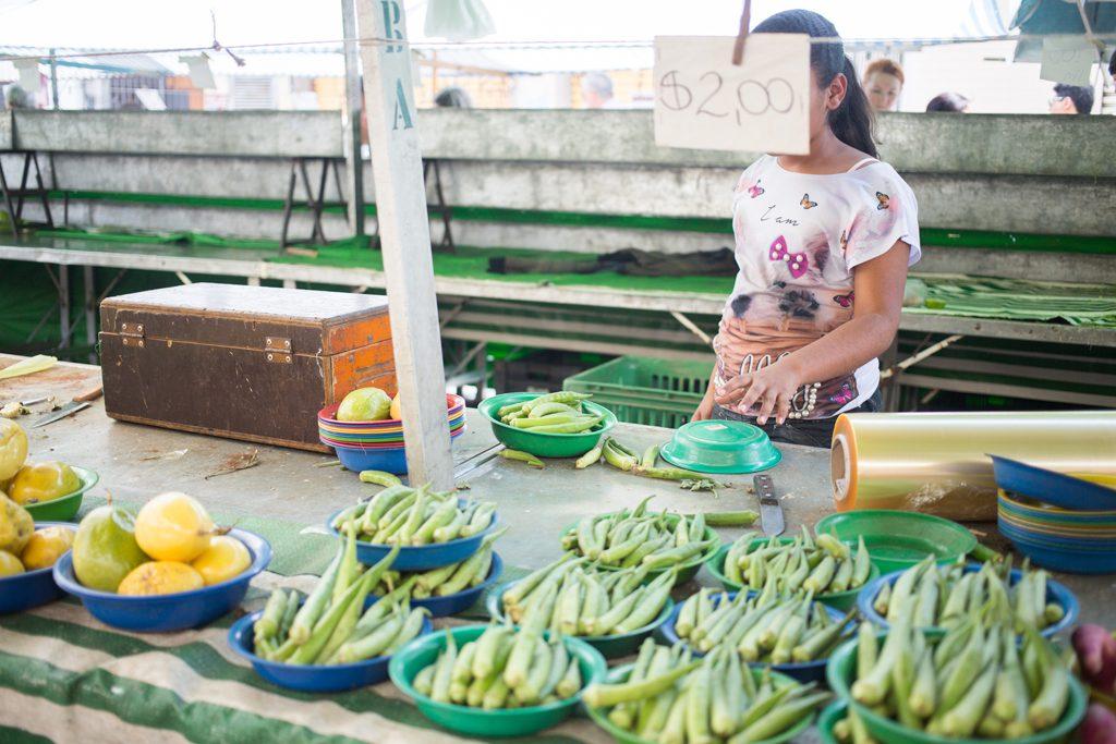 Imagem mostra menina vendendo bananas em barraca de feira livre. Seu rosto está encoberto