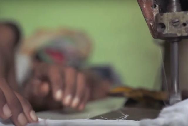 Criança trabalha com máquina de costura em confecção: atividade perigosa agrava a violação de direitos.