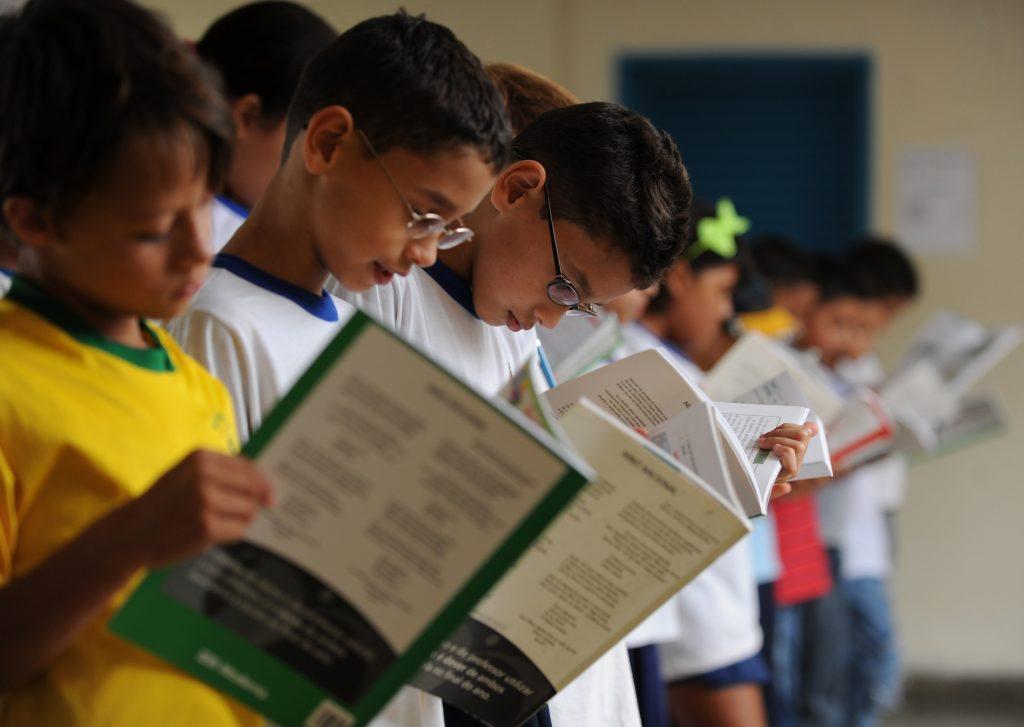 Crianças fazem leitura coletiva em escola. Crédito: EBC