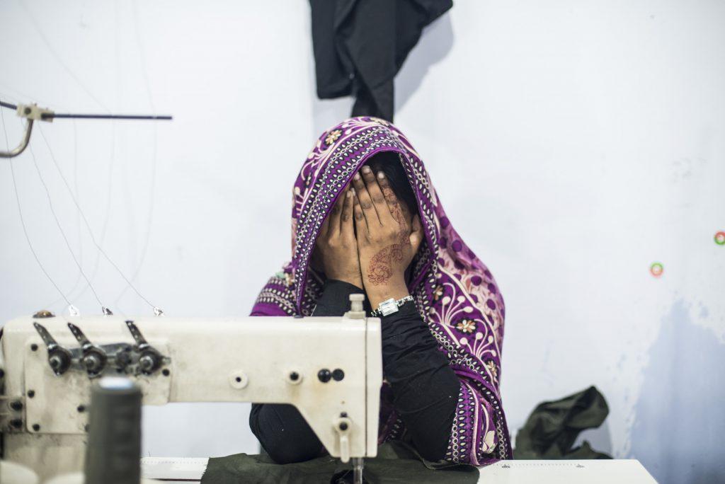 Menina esconde o rosto em fábrica de roupas de Daca, Bangladesh