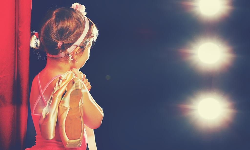 Criança de costas segura sapatilhas de balé em cima do palco enquanto observa a plateia