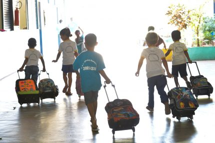 crianças de costas indo para a escola arrastando suas mochilas com rodinhas