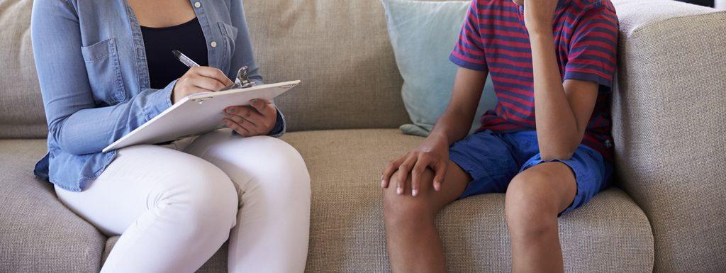 Qual é o papel do psicólogo no combate ao trabalho infantil? A foto mostra uma prossional conversando com um garoto, ambos sem identificação dos rostos, para preservar a imagem. Crédito: iStock