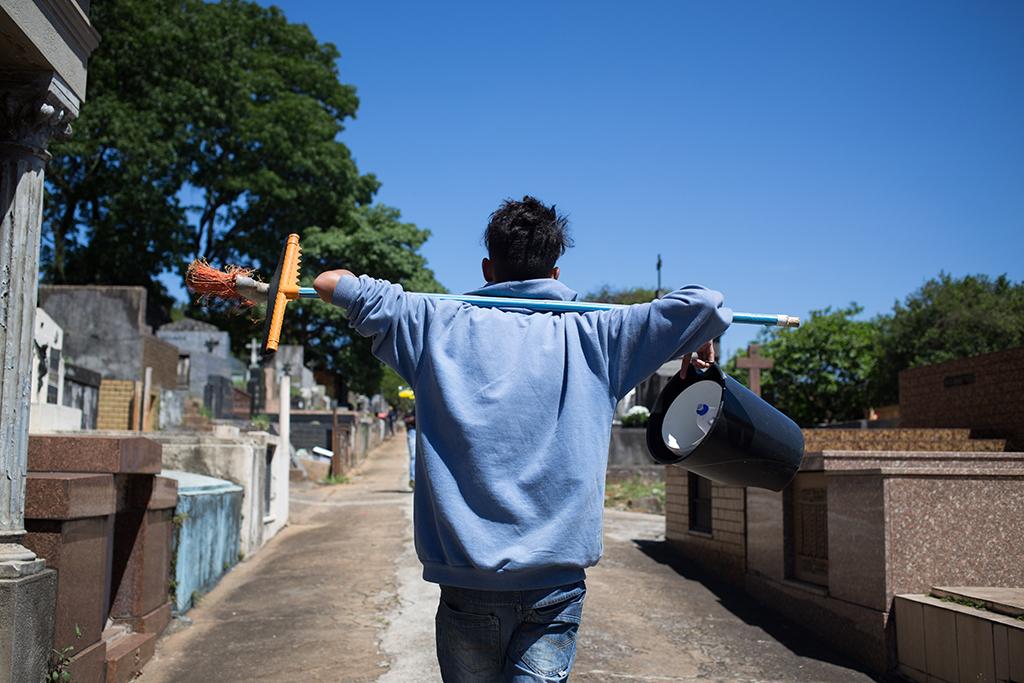 Garoto de costas carrega utensílios de limpeza no Cemitério do Araçá, em São Paulo