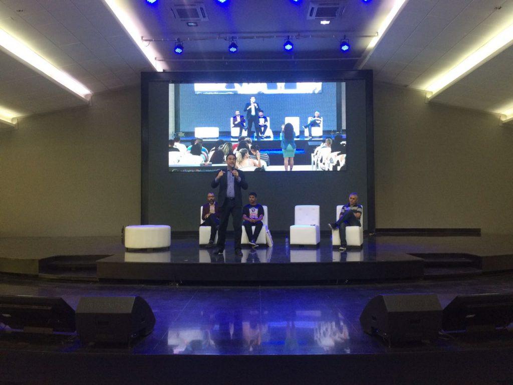 Palestrante em palco com luz azul fala no simpósio