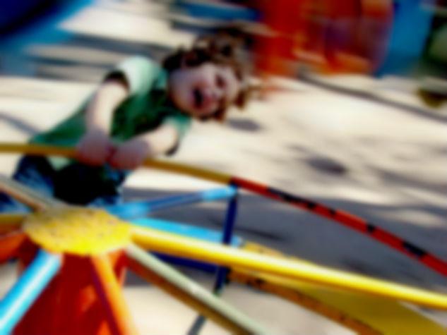 Crianças brinca no gira-gira. Imagem borrada em movimento