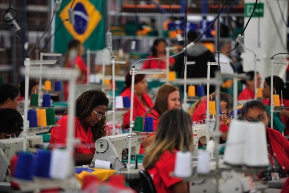 Mulheres trabalham com costura em fábrica. Cada uma sentada em sua mesa, com macacões laranjas