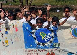 Crianças em passeata de escola carregam cartaz defendendo a paz no mundo