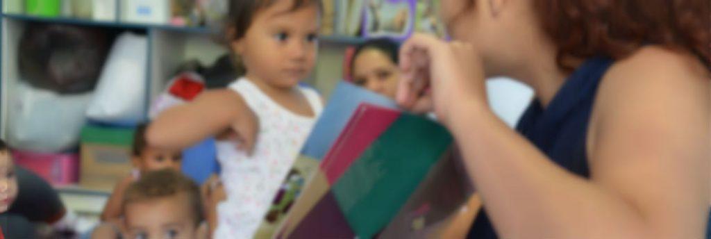 Mulher mostra livro para criança de cerca de 3 anos