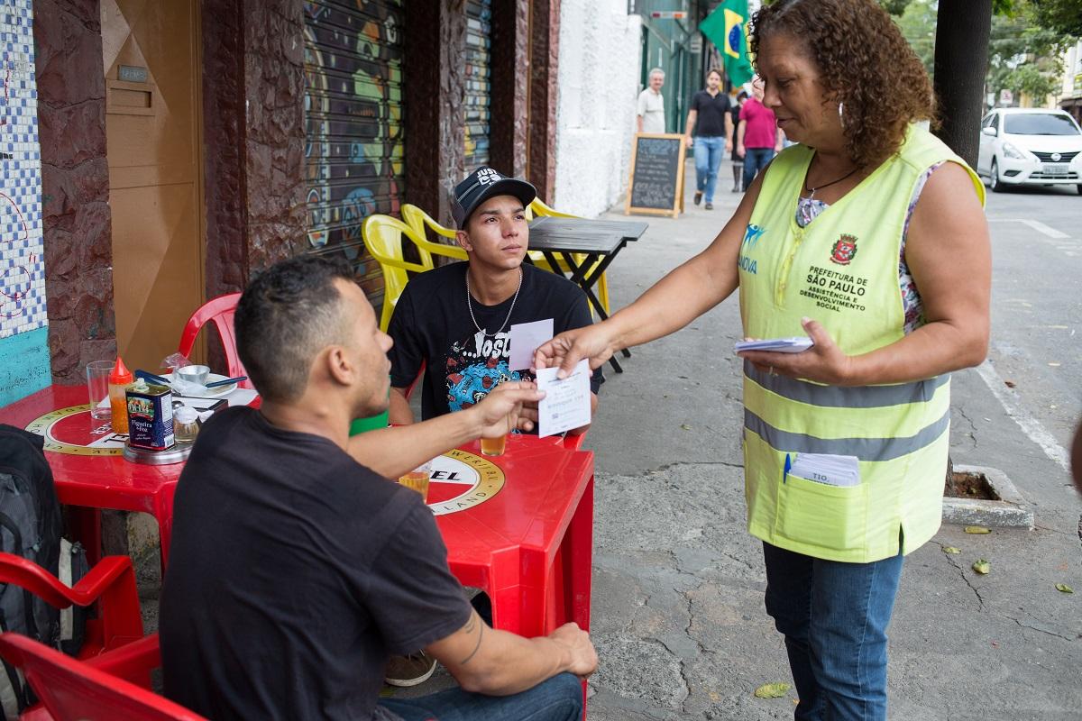 Orientadora social abordagem clientes de bar em mesa na Vila Madalena