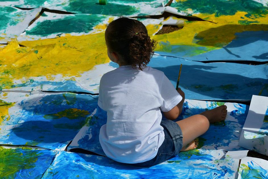 menina sentada sobre a bandeira do brasil