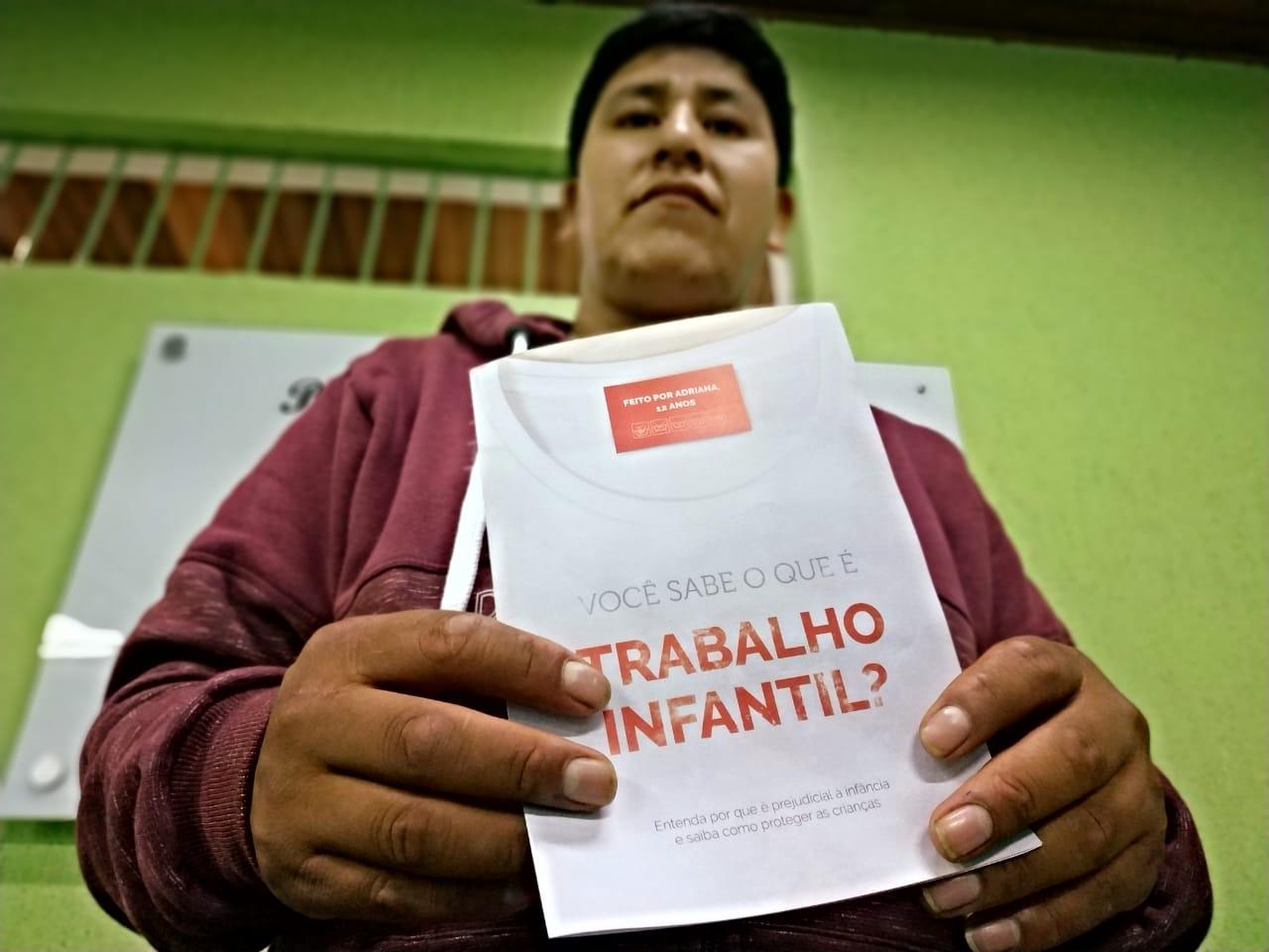 Homem boliviano segura folder da campanha trabalho infantil na indústria da moda.