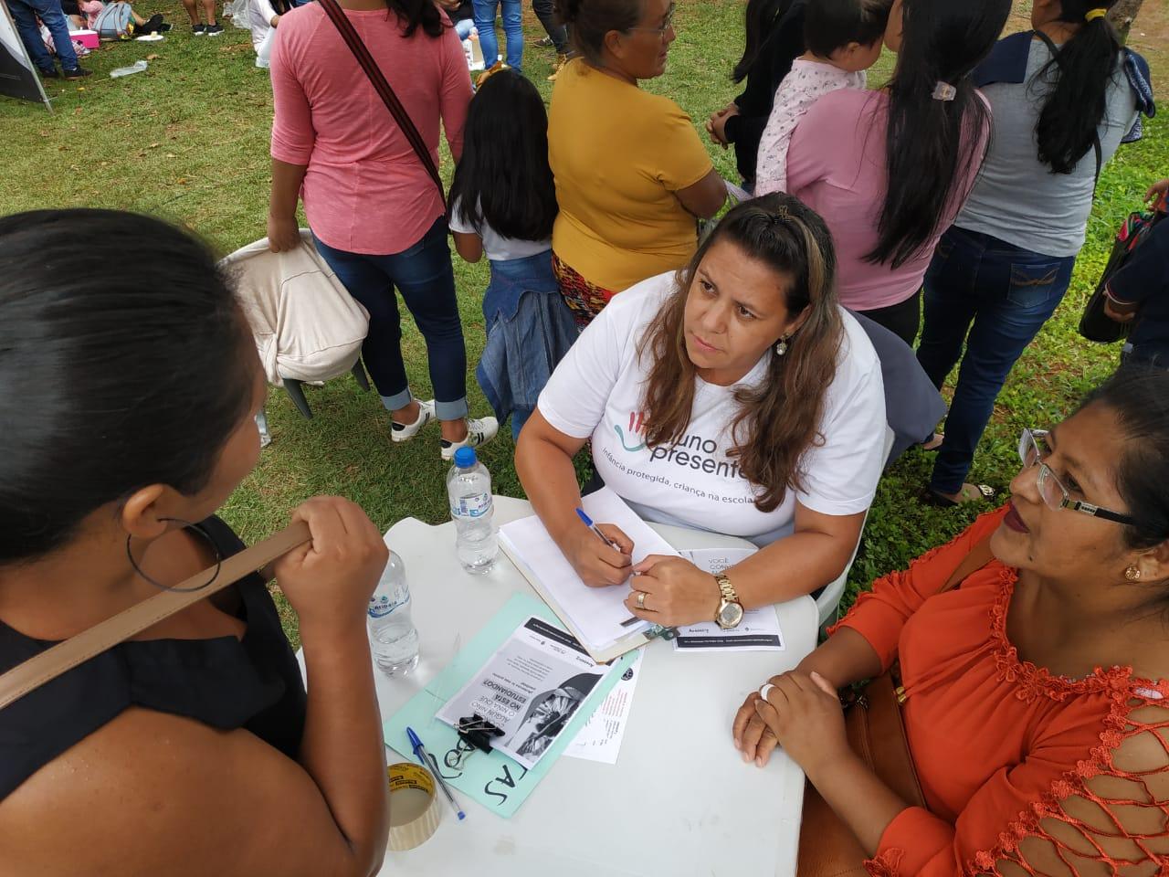mulher sentada atende duas outras mulheres que estão de pé em tenda montada em festival